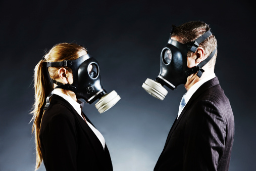 Couple in gas masks face off confronting each other