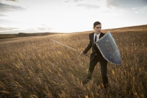 Alert businessman with sword and shield outdoors